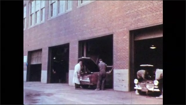 1960s: Boys and teachers work on cars in garage bays. Teacher talks with boys as they look at engine.