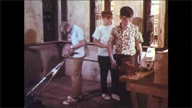 1960s: Boy takes gauge out of cabinet. Boy adjusts lever on lawnmower. Boy inserts gauge into engine, pulls engine cord.