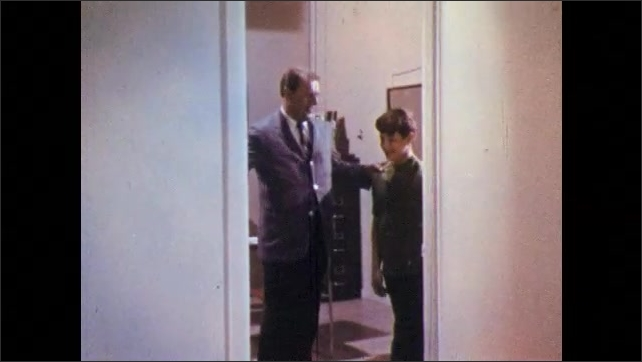 1960s: Man and boy get up from table, man escorts boy out of office, they shake hands, boys walks away.
