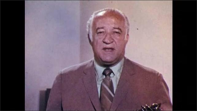 1960s: Man talks.