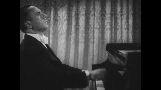 1940s: hands play piano, hands are reflected in piano front above keyboard, Jose Iturbi plays piano, seen from the side