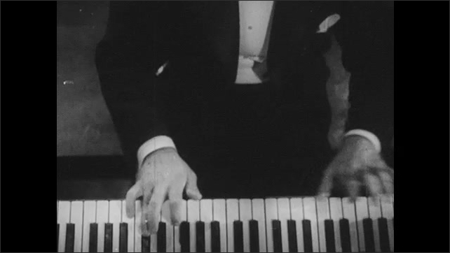 1940s: hands play piano, hands are reflected in front of piano above keyboard, hands play piano seen from above