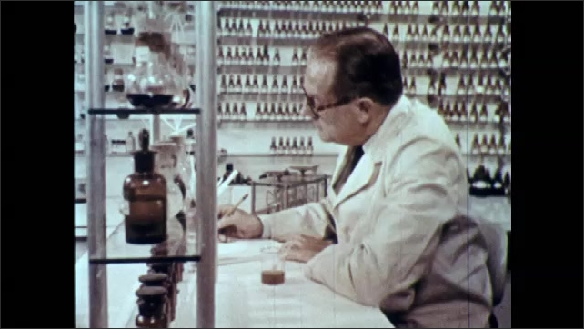 1960s: UNITED STATES: perfumer works in fragrance room. Bottles of oils on shelf. Man takes bottle from shelf