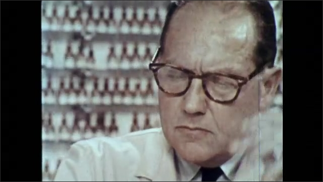 1960s: UNITED STATES: perfumer sniffs scents on strips. Hand chooses bottle of fragrance.