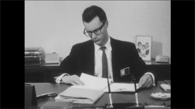 1960s: UNITED STATES: man in suit sits at desk in office. Personnel Manager works at desk. Man looks through papers at desk.