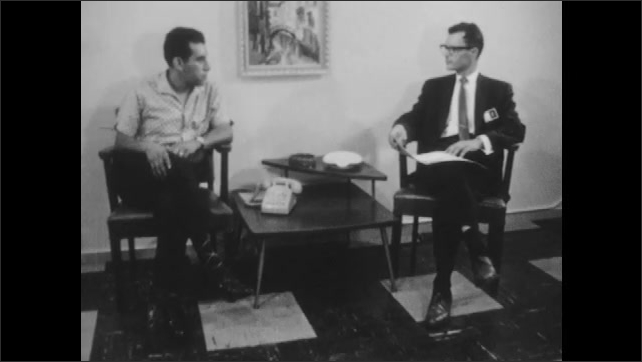 1960s: UNITED STATES: man has interview for job promotion. Close up of man's face in meeting. Man wearing glasses. Man nods head.