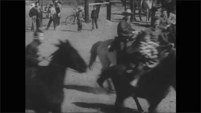 1940s: Cowboy talks to toddler eating hotdog. Cowboy rides past boys and girls on horseback. Women sit on hill. Man waves hat. Children on horses race across rodeo arena.