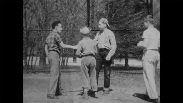 1940s: Two boys on baseball field fight over mitt. Boy talks. Boys fight over mitt as other boys come to intervene. Boy points passed everyone. School books on ground.