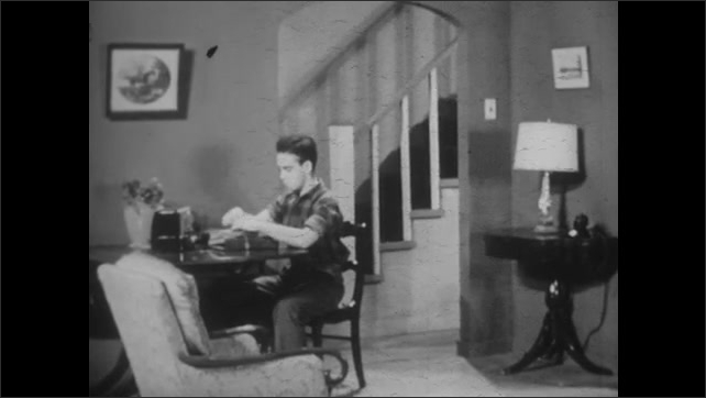 1940s: Boy enters living room with school books and sits down at table to look at them.