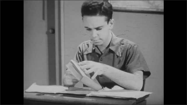 1940s: Boy sits at school desk reading book. Boy puts books in desk then grabs other book to read while taking notes.