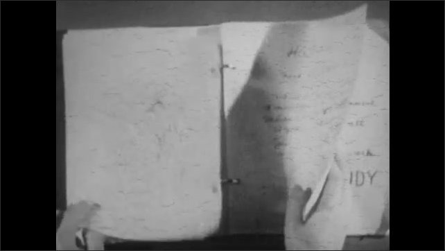 1940s: Boy sits at desk in bedroom, reading notes, then he looks up and nods. Boy flips through pages of notebook. Boy opens notebook and flips through pages.