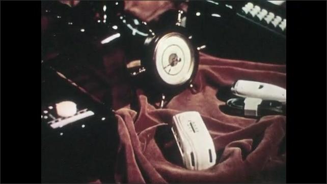 1940s: Various items sit on spinning velvet sheet. Turning gears.