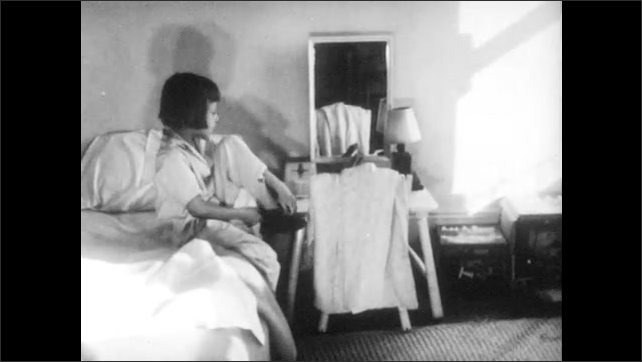 1940s: Calendar on wall. Girl puts on slippers, gets up from bed. Girl runs from bed. Girl runs through room, searches on ground.