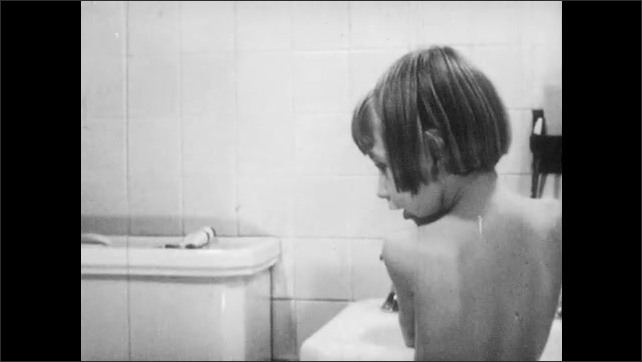1940s: Girl carries cat into bathroom, puts cat on toilet, takes off robe. Girl washing hands in sink. Close up, cat grooming itself. Hands rub soap on washcloth.