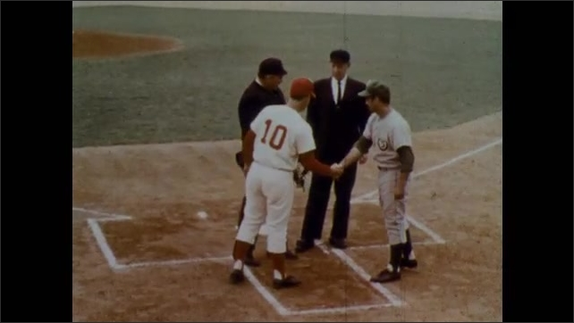 1970s: Baseball coaches, umpires shake hands. Coaches and umpires shake hands, look at papers.