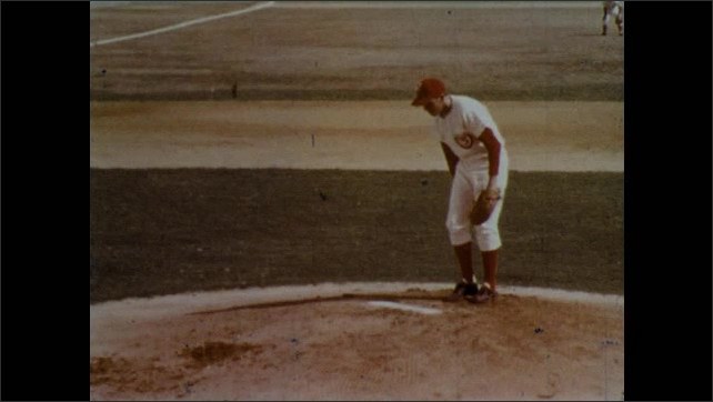 1970s: Baseball pitcher throws ball. Pitcher throws ball. Slow motion of pitch. View of pitcher's legs.