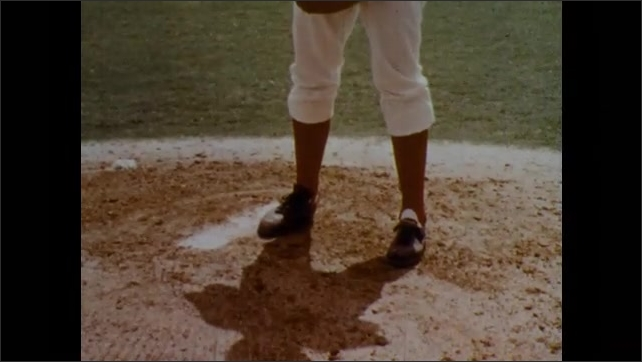 1970s: Baseball players on field. Pitcher on mound. Players at plate. Pitcher moves to throw ball. Player runs to plate. Feet on mound. Pitcher moves to throw. Pitcher on mound, batter in background.