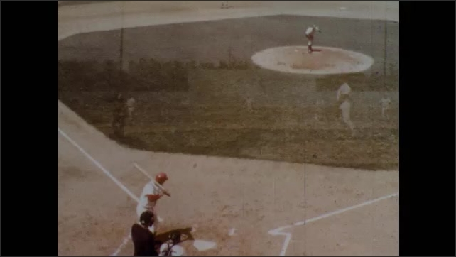 1970s: Pitcher on mound. Umpire yells behind pitcher, player runs to base. High angle view og mae, putcher throws to batter. Batter walks to base.