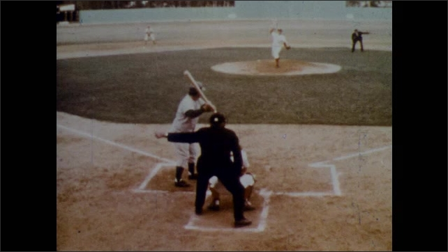1970s: Rear view of batter at plate. Runner on base. Pitcher winds up. Rear view of batter, image freezes. Pitcher throws. Batter hits. Players running. Player runs bases. Player throws to base.