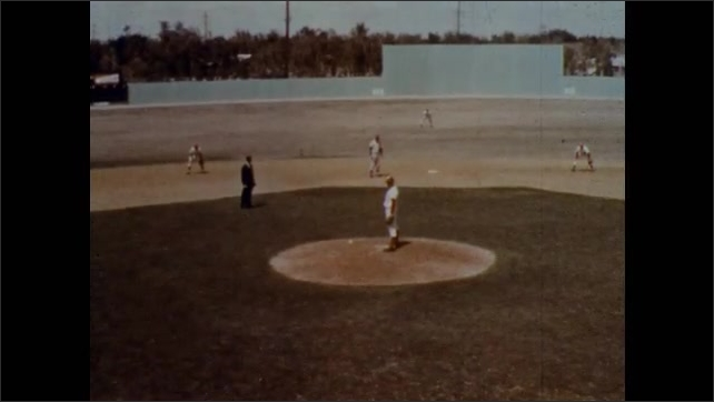 1970s: Wild pitch stuck in fence and umpire calls the ball dead. The batter is sent to first base. Pitcher pitches with runners on first and second base. Batter hits the ball into the infield.