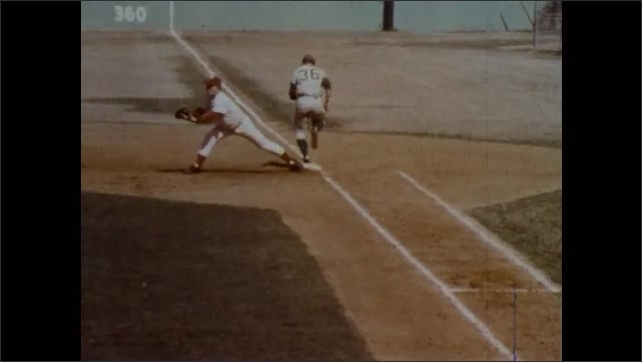 1970s: Umpire races into position to watch a play at first. One umpire covers first base and another umpire runs to cover third base.