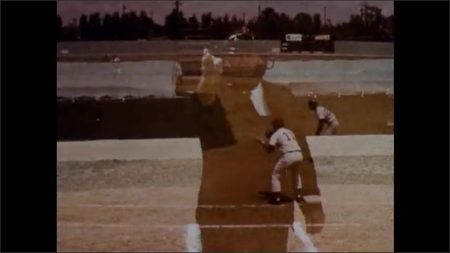 1970s: Umpire makes a variety of calls from home base. Runners at first and second. Shortstop catches the ball.