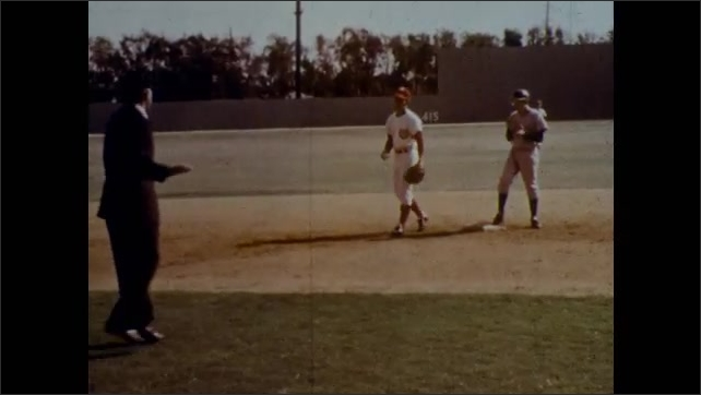 1970s: Umpire calls the runner safe after fielder appeal. Runner on second claps in celebration. Runners on second and third as pitcher winds up.