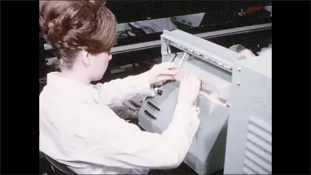 1960s: Woman seated at machine presses button and writes on sheet of paper. Woman wipes machine and moves carriage-type piece into position.
