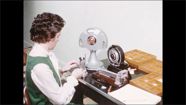 1960s: Woman lifts piece of machine and places metal piece on frame. Woman works at Digital Fibrograph machine with counter. Woman seated at table works.