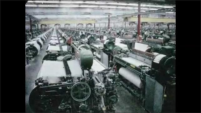 1960s: Woman checks threads in machine. Machines weave threads into fabric.