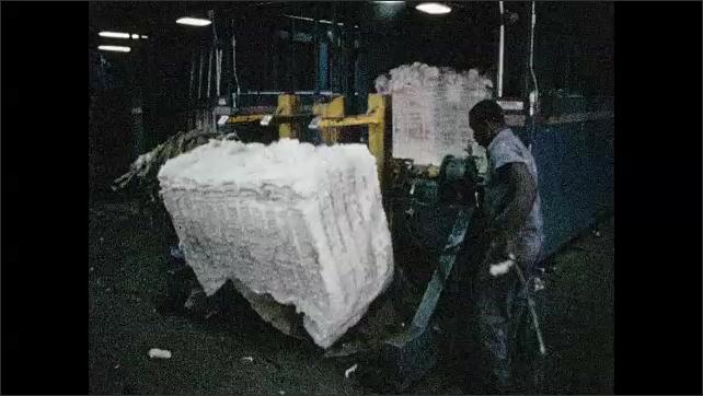 1960s: Man cuts straps on bale of cotton, raises bale on lift, pushes bale.