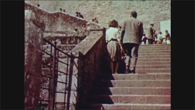 1960s: EUROPE: man talks to lady on wall. Lady and man walk up steps. Tourists visit historical building. Windows on building.