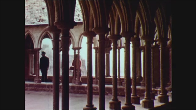 1960s: EUROPE: tourists visit interior of historical building. Lady and man stand inside courtyard
