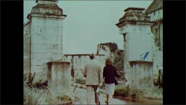 1960s: Low angle view of cathdral. Man and woman walk toward castle ruins.