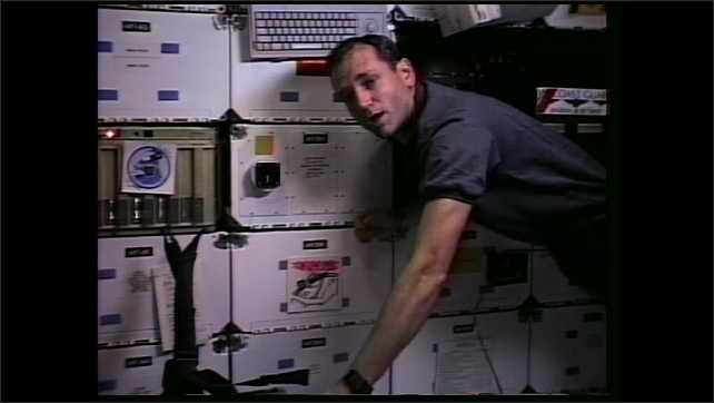 1990s: Man floats in zero gravity and speaks. Astronaut points to altimeter on wall of space shuttle cabin and speaks.