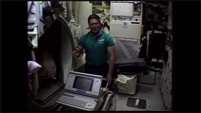 1990s: Man floats in zero gravity near computer and speaks.