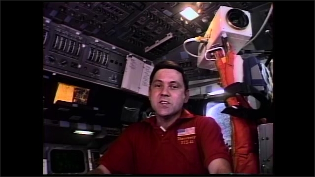 1990s: Astronaut sits at space shuttle controls and speaks.