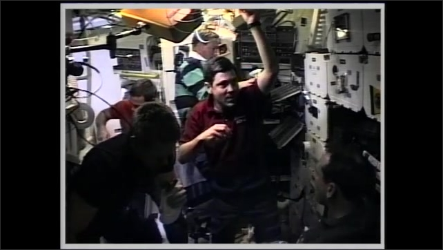 1990s: Astronauts share food and eat in zero gravity on space shuttle. Man floats near cabinets in cabin and speaks.
