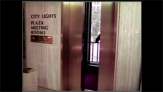 1990s: Man in uniform walks onto elevator in office building. Man looks out window as elevator moves upwards.