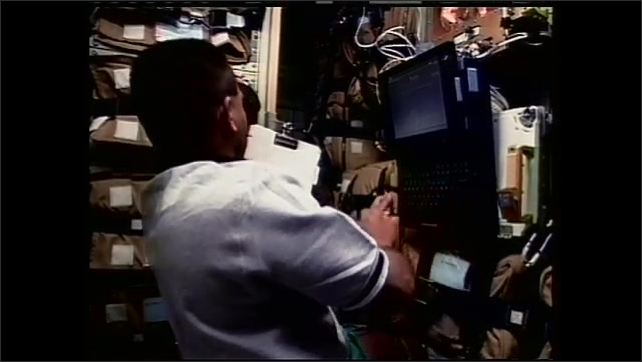 1990s: Astronaut floats upward on space station. Man works on computer in zero gravity. Man flips through folder of papers on space station.