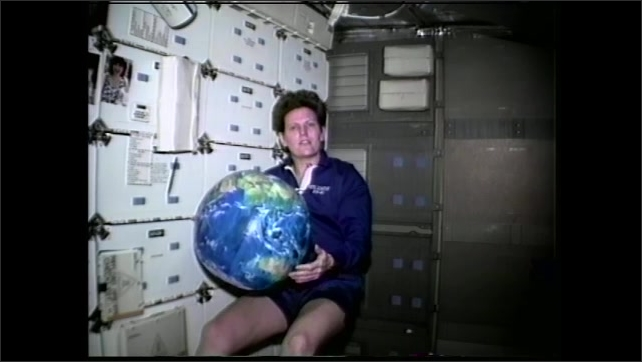 1990s: Astronaut floats an space shuttle with beach ball of the Earth. Woman floats with globe and speaks. Beach ball transforms into computer animated Earth.