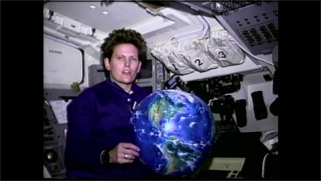 1990s: Astronaut floats in space shuttle with beach ball of the Earth and talks. Earth from space. Grass blows in agricultural fields.