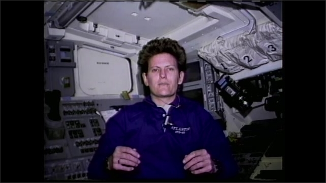 1990s: Astronaut floats in space shuttle cockpit and talks.