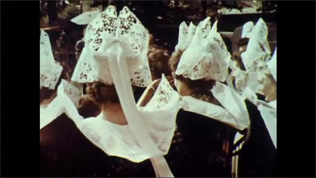 1960s: Tilt down exterior of church, crowd outside church. Tracking shot, group of women in costume.