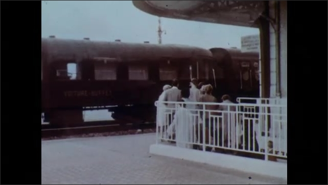 1960s: People emerge from underground staircase at train station. Man and woman greet each other near moving train. Car pulls into driveway of home. Woman greets family near front door.