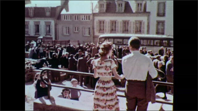1960s: Man and woman stand at railing, man talks. People at market on street. Woman points and talks.