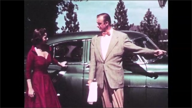 1950s: UNITED STATES: man talks to lady by car. Men watch lady on film set