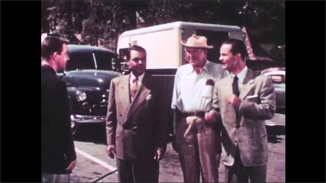 1950s: Four men stand near trucks on film set and talk. Assistant runs toward men and speaks. Man straightens tie and walks toward set. Assistant talks to director.