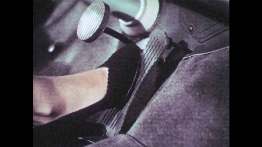1950s: UNITED STATES: close up of foot on pedal. Rear view of men in car. Side view of men in car. Car drives through town