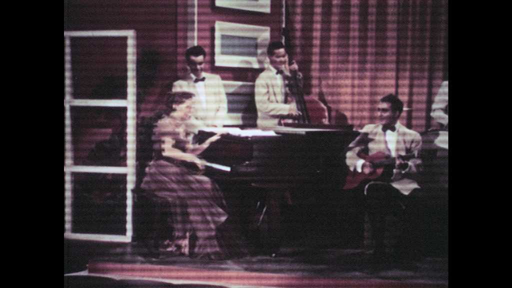 1950s: UNITED STATES: lady stands up from piano. Lady plays guitar on stage. Lady sings on stage.